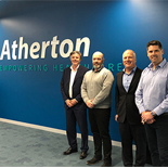Representatives standing infront of the Atherton sign