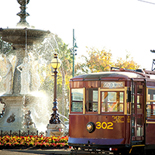 The old tram passes the fountain